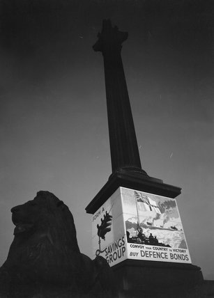 Nelson's Column in Trafalgar Square, London, with its plinth covered with wartime posters advertising Defence Bonds in 1940.