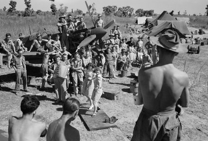RAF personnel watch Carolyn Wright and Roberta Robertson tap-dancing during an impromptu ENSA [Entertainments National Service Association] show at an airfield in Burma, February 1945.