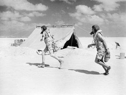 Two pilots of No. 274 Squadron sprinting to their aircraft during a practice scramble at El Amriya, Egypt, October 1940.