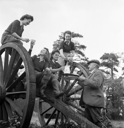Land Girls enjoy a hot cup of tea after a hard day of rat catching on a Sussex farm during 1942.