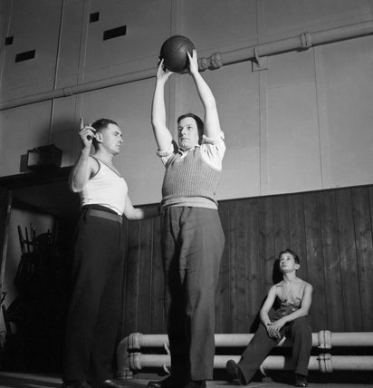 A patient receiving Physical Training instruction at Queen Mary's Hospital in Roehampton, London, during his rehabilitation from the loss of both his legs in 1944.