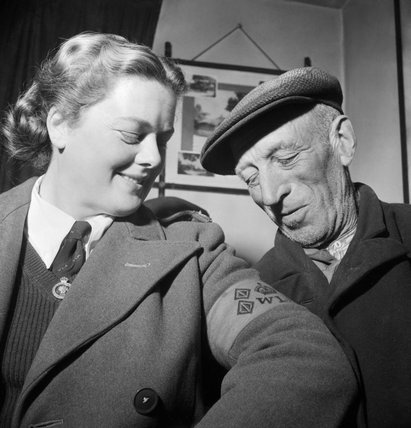 Land Girl Rosalind Cox shows her Women's Land Army armband to local farm labourer Sam Scott in the