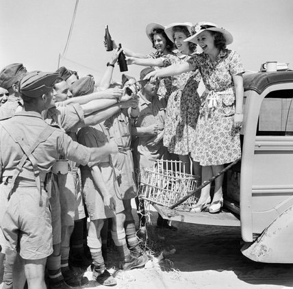 ENSA (Entertainments National Service Association) 'glamour girls' distribute cigarettes and beer to the troops in North Africa, 26 July 1942.