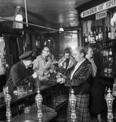 Mrs Pitt, wife of the landlord, pours a pint of beer for a naval officer in the saloon bar of 'The Cricketers' pub in Brighton during 1944.