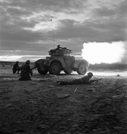 A Daimler armoured car opens fire in the gloom of early morning at the start of the battle for Tripoli, 18 January 1943.