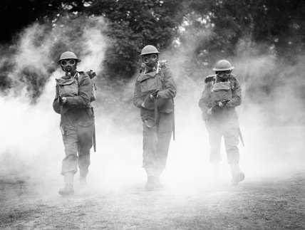 Irish Guards wearing gasmasks advance through smoke with 'tommy guns' at the ready, at Nooks Head near Woking in Surrey, 8 July 1940.