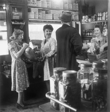 The Reverend Joseph Stephens stops in a grocer's shop in Silvertown, London, to buy some cherries, 1944.