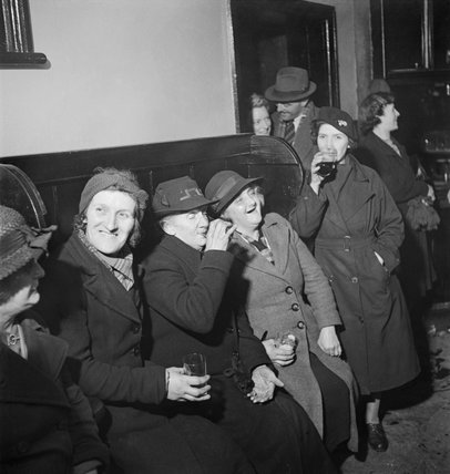 A group of women enjoy a drink and share a joke at the Wynnstay Arms, Ruabon, Benbighshire, Wales, 1944.