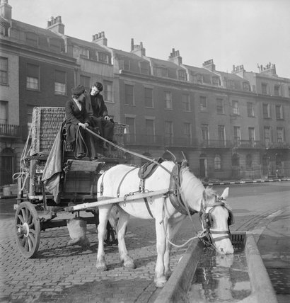 Horse-drawn delivery van of the London, Midland and Scottish railway halted in a sqaure in Bloomsbury during 1943 to allow the horse to get a drink.