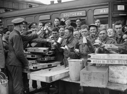 Troops evacuated from Dunkirk enjoying tea and other refreshments at Addison Road station in London, 31 May 1940.