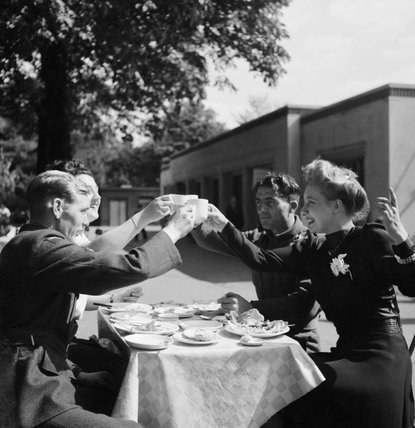 Four friends raise their tea cups in a toast to celebrate an afternoon's fun in Hyde Park, London during their 'stay at home holiday' in 1943.