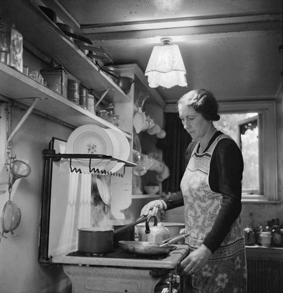 Mrs M Hasler cooks breakfast for her invalid husband in their home in Barnes, Surrey, during 1942.