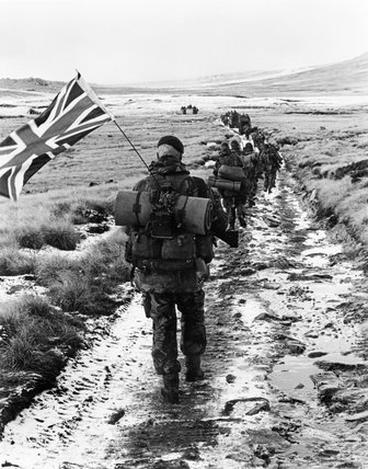 45 Royal Marine Commando marches towards Port Stanley during the Falklands War, 1982. Marine Peter Robinson carrys the Union Flag on his pack.