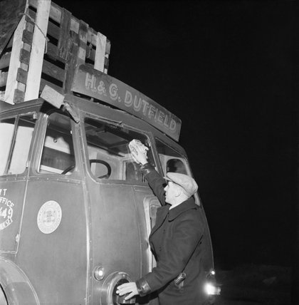 A long-distance lorry driver cleaning the windscreen of his 7-ton Leyland lorry before resuming his journey in 1944.