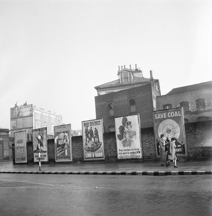 Ministry of Information posters on display in a British street during 1942.