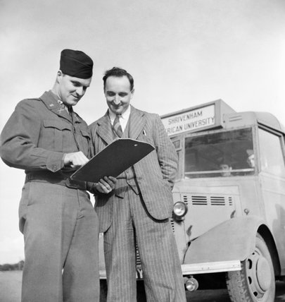 Corporal Thomas Gibson checks a schedule with British driver Gwyn Cartwright at the US Army University, Shrivenham in 1945.