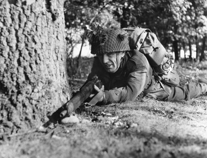 Paratrooper of the 16th Airborne Division (Territorial Army) takes up a firing position in a wood during Exercise King's Joker at the Stanford Parachute Training Area, September 1953.