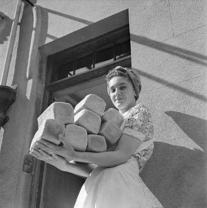 Barbara Smaile, one of the kitchen staff at the Women's Land Army break house at Torquay in 1944, brings in freshly baked bread.
