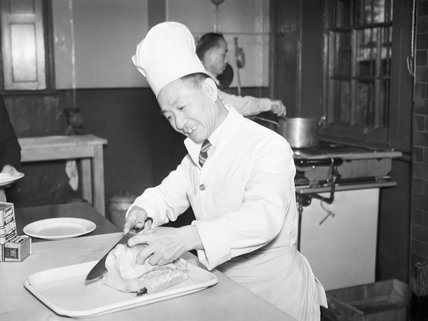 A Chinese merchant sailor, who served as chief cook, carves meat in the kitchen of the Chinese sailors' convalescent home in Liverpool, 1943.