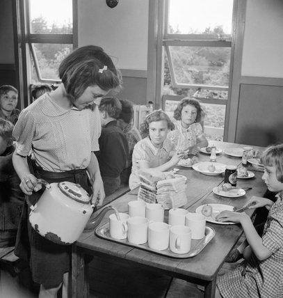June Beale pours tea for other evacuee children in the dining hall at Marchant's Hill school, Hindhead, Surrey, 1944.