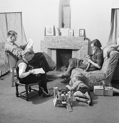 The Chillingworth factory relax in front of the fire in the living room of their suburban London home.