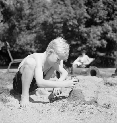 As part of the 'Holiday at Home' scheme, a young boy puts the finishing touches to the sand castle he is building in the sunshine in Regent's Park, London, 1943.