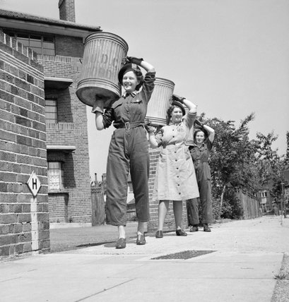 Salvage workers from the Women's Voluntary Sservice (WVS) in East Barnet, Hertfordshire, during 1943, carrying bins containing kitchen scraps that will be distributed to local farmers as food for pigs
