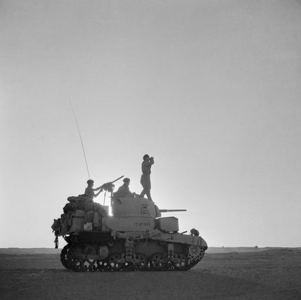 The commander of a British Stuart tank scans the horizon, silhouetted against the setting sun, 6 September 1942.