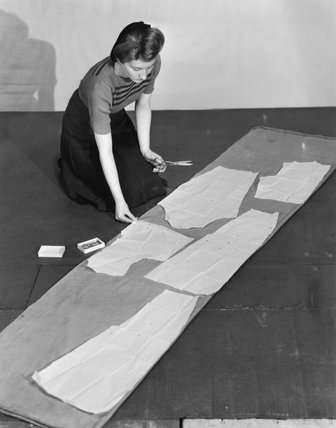 A woman cuts out sections of material from a large piece of curtain or other such fabric, using paper patterns as a guide, 1942.