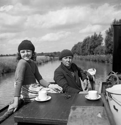 Mrs Gribbis and her daughter Valerie enjoy a lunchtime cup of tea as they steer the 'butty', being towed by Mr Gribbis' narrowboat on the Grand Union Canal during 1944.