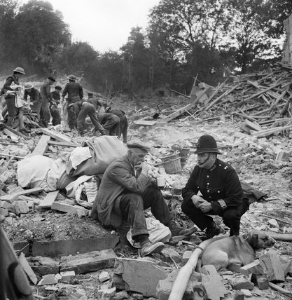 A police constable comforts a man sitting amongst the rubble of his house destroyed by a V1 Flying Bomb in 1944.