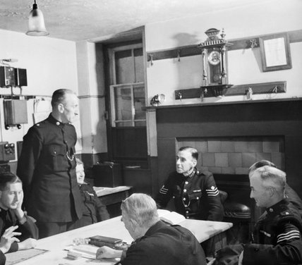 At Wotton-under-Edge police station, Sergeant Auger (seated at the head of the table) chats to some of the twenty-two Special Constables who have joined the three regualrs in keeping law and order in the town, 1944.