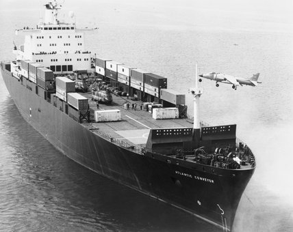 A Royal Navy Sea Harrier piloted by Lieutenant Commander Tim Gedge, Commanding Officer of No. 809 Naval Air Squadron, approaches the Cunard container ship ATLANTIC CONVEYOR to test its recently installed flight deck at Devonport, 25 April 1982.