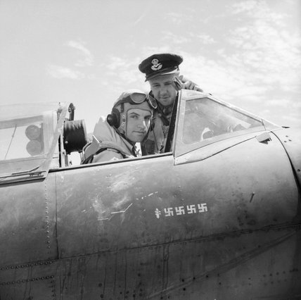 Flight Lieutenant Dennis Barnham of No. 601 Squadron RAF in the cockpit of his Supermarine Spitfire Mk VB at Luqa, Malta, with Pilot Officer M H Le Bas, June 1942.</br></br></br>