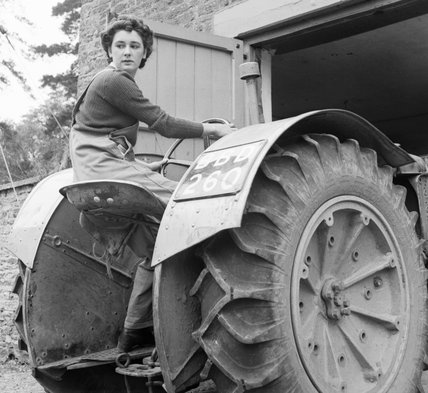Anne Keys of the Women's Land Army reverses a tractor out of a shed during her training at the Northampton Institute of Agriculture near Moulton in 1942.