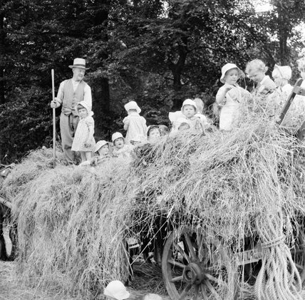 A group of young evacuees sit on a hay cart outside Chapel Cleeve Nursery in Washford, Somerset, 1942.