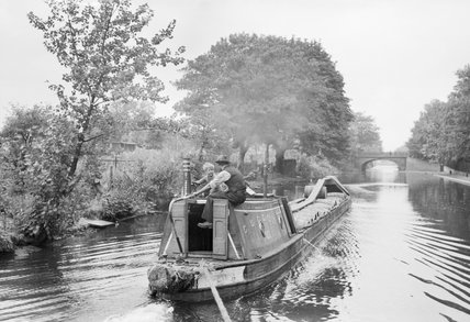 A canal boat loaded with fruit pulp travels along the leafy Regent's Canal, on its way to the Grand Union Canal in 1944.