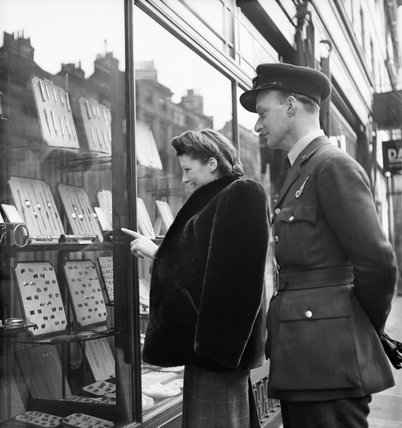 Newly-engaged Marcelle Lestrange and her fiance Flying Officer Harold Lackland Bevan looking for a suitable engagement and wedding ring in London during March 1943.