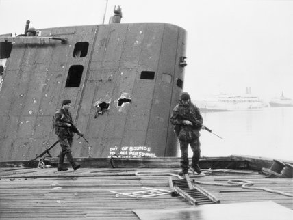 Royal Marines patrol past the abandoned Argentine submarine SANTA FE on South Georgia, 28 May 1982.
