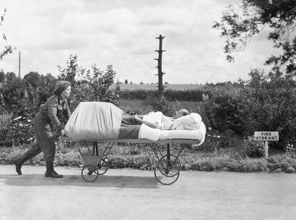 Lance Corporal Whitefield of the Auxiliary Territorial Service pushes an injured RAF armourer on a trolley around the grounds of the Robert Jones and Dame Agnes Hunt Orthopaedic Hospital, Oswestry during 1944.