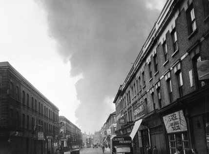 A cloud of smoke rises in the distance after a V1 Flying Bomb lands in the Norwood area of London during 1944.