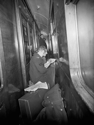 A member of the Women's Royal Air Force reads a magazine as she sits on her luggage in the corridor of a train in 1944.