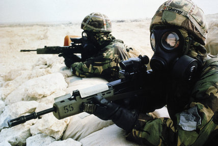 Two British soldiers in NBC [Nuclear Biological and Chemical] equipment, pose with their SA80 rifles during a training exercise in Saudi Arabia before the start of operations in Kuwait, 1990 - 1991.