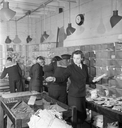 Wrens and ratings of the Royal Navy at work in a Fleet Mail Office at a naval shore establishment in England during 1944.