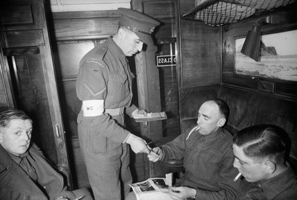 A Lance Corporal of the Royal Engineers checks the tickets and passes of passengers in a compartment of a train travelling between London and Scotland during 1944.