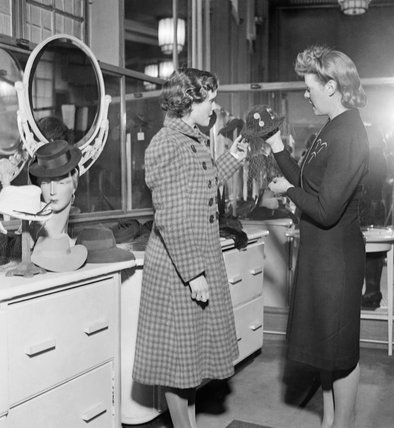 Hilda Chillingworth (left) looks at hats in a shop during her lunch brea in London during 1942.