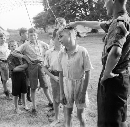 Boy Scouts queue up for their morning inspection at a fruit-picking camp near Cambridge in 1943.
