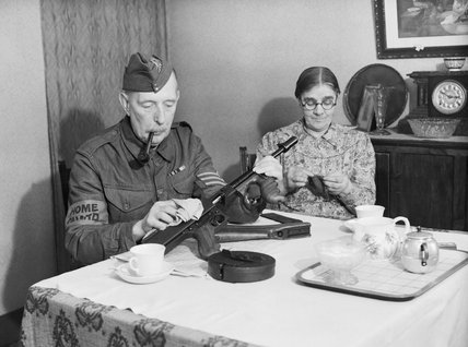 A veteran sergeant in the Dorking Home Guard cleans his Tommy gun at the dining room table, before going on parade, 1 December 1940.