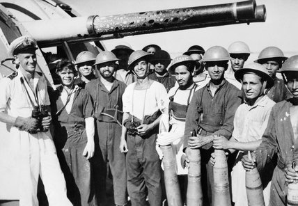 Lieutenant M H Jerram with the gun crew of the Indian sloop NARBADA at Myebon, Burma, 1945.