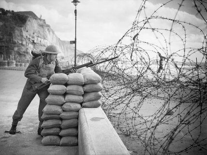 Posed portrait of a soldier with rifle and bayonet standing watch behind beach defences 'somewhere in Southern England', 15 October 1940.